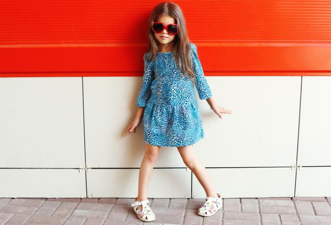 Beautiful little girl model wearing a leopard dress and sunglass
